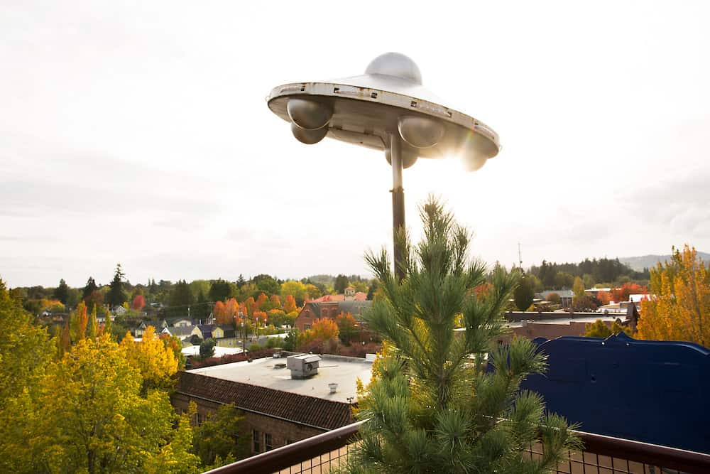 Rooftop UFO sculpture in October, with beautiful fall leaves in the background.